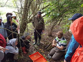 Professor Stothard (seated) teaching fresh water sampling to MSc students